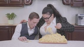 Portrait of a confident plump woman in the kitchen at the table in front of plate with noodles. The girl trying to feed. Portrait of a confident plump woman in stock video