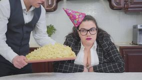 Portrait of a confident plump woman at the table in the kitchen. Slim cute man putting a big plate with noodles in front stock video
