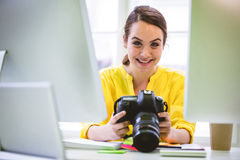 Portrait of confident professional with digital camera and computer at office Royalty Free Stock Image