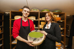 Portrait of confident salespeople showing cheese in shop Royalty Free Stock Photography