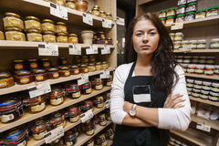 Portrait of confident saleswoman standing arms crossed in grocery store Royalty Free Stock Images