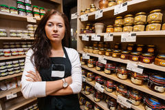 Portrait of confident saleswoman standing arms crossed in grocery store Stock Photography