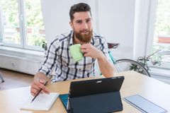 Portrait of a confident self-employed young man sitting at desk royalty free stock photography