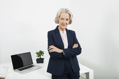 Portrait of confident senior businesswoman with arms crossed in office Stock Photos