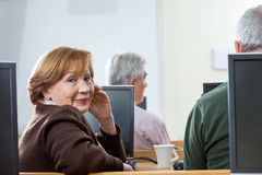 Portrait Of Confident Senior Woman Sitting In Computer Class Stock Images
