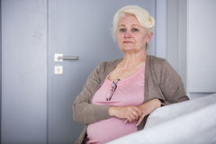 Portrait of confident senior woman sitting in house Stock Image