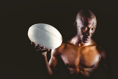 Portrait of confident shirtless sportsman holding rugby ball Royalty Free Stock Photos