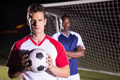 Portrait of confident soccer player holding ball with rival athlete. Standing against goal post stock photos