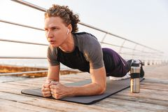 Portrait of a confident sportsman doing plank exercise stock images