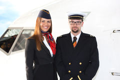 Portrait of confident stewardess and pilot standing against plane. Portrait of confident stewardess and pilot standing against the plane Royalty Free Stock Image