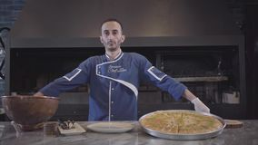 Portrait of a confident successful chef in a blue uniform standing next to a delicious, appetizing dish in the kitchen. Portrait confident successful chef in a stock video footage