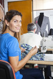 Portrait Of Confident Tailor Sitting At Workbench. Rear view portrait of confident female tailor sitting at workbench in factory with colleague in background Stock Photography