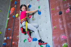 Portrait of confident teenage girl practicing rock climbing. In fitness studio royalty free stock photography