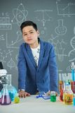 Portrait of Confident Teenage Pupil. Confident teenage pupil wearing T-shirt and jacket leaning on school desk and looking at camera while having chemistry class Stock Photo