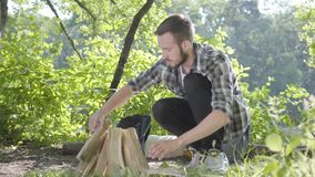 Portrait confident traveler puts firewood for the fire. Handsome man in a plaid shirt prepares to make a fire outdoors. Confident traveler puts firewood for the stock video footage