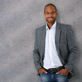 Portrait of confident and trendy black businessman. Leaning against gray concrete wall Royalty Free Stock Images
