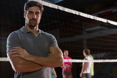 Portrait of confident volleyball player with teammates in background. Portrait of confident male volleyball player with teammates in background at court Stock Photography