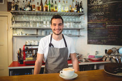 Portrait of confident waiter with coffee at counter in cafe Stock Photo