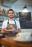 Portrait of confident waiter with cupcakes at coffee house Royalty Free Stock Image