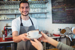 Portrait of confident waiter serving coffee to customer at cafe Royalty Free Stock Images