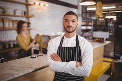 Portrait of confident waiter standing with arms crossed at  coffee shop. Portrait of confident waiter standing with arms crossed against waitress working at Royalty Free Stock Image