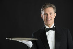 Portrait Of Confident Waiter In Tuxedo With Serving Tray. Isolated over black background Royalty Free Stock Photos