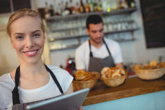 Portrait of confident waitress with digital tablet. Standing with colleague at cafe Royalty Free Stock Photos