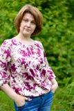 Portrait of confident woman against a background of green foliage. Portrait of a confident woman against a background of green foliage Stock Images