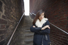 Portrait of confident woman with arms crossed standing against steps at London, England, UK Royalty Free Stock Images