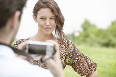 Portrait of confident woman being photographed by man in park Stock Images