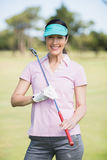 Portrait of confident woman carrying golf club. While standing on field Royalty Free Stock Photo