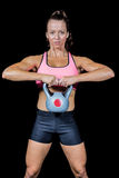 Portrait of confident woman exercising with kettlebell. Ag against black background Royalty Free Stock Photos