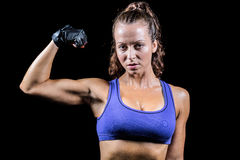 Portrait of confident woman flexing muscles. Against black background Royalty Free Stock Image