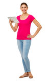 Portrait Of Confident Woman Holding Digital Tablet. Full length portrait of confident woman holding digital tablet against white background. Vertical shot Royalty Free Stock Photography