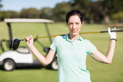 Portrait of confident woman holding golf club. While standing on field Stock Photos