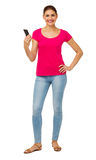 Portrait Of Confident Woman Holding Smart Phone. Full length portrait of confident woman holding smart phone against white background. Vertical shot Royalty Free Stock Photo