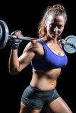 Portrait of confident woman lifting crossfit. Against black background Stock Image
