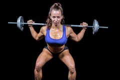 Portrait confident of woman lifting crossfit. Against black background Stock Images