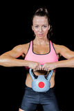 Portrait of confident woman lifting kettlebell. Against black background Royalty Free Stock Image