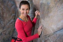 Portrait of confident woman practicing rock climbing. In fitness studio Stock Photos