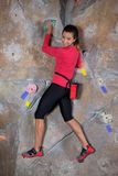 Portrait of confident woman practicing rock climbing. In fitness studio Royalty Free Stock Image