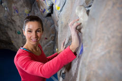 Portrait of confident woman practicing rock climbing. In fitness studio Royalty Free Stock Images