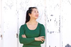 Confident woman standing with arms crossed looking away Stock Photo