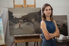 Portrait of confident woman standing with arms crossed. In drawing class Royalty Free Stock Photos