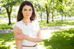 Portrait of confident woman. Standing on grassland in park Stock Photo