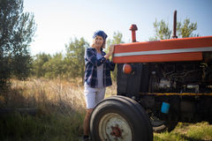 Portrait of confident woman standing near tractor in olive farm. On a sunny day Royalty Free Stock Photo