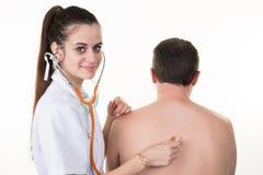 Confident woman practitioner checking heart beat of man patient. Portrait of confident women practitioner checking heart beat of men patient stock image