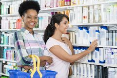 Woman Smiling While Friend Choosing Product In Pharmacy. Portrait of confident women smiling while friend choosing product in pharmacy Stock Photos