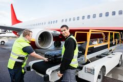 Worker Smiling While Colleague Unloading Luggage On Runway Royalty Free Stock Photos