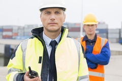 Portrait of confident worker standing with coworker in background at shipping yard Stock Image